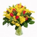 Bouquet of red red tulips and mimosa in green complementary