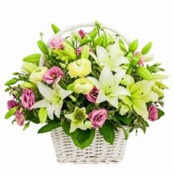 Armonia di fiori dai toni chiari in bel cesto di vimini bianco