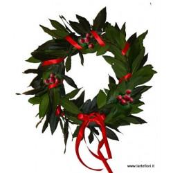 Corona de hojas de laurel con las bayas y cinta roja