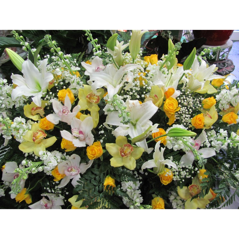 Pillow of flowers composed with orchids, yellow,white orchids,white lilies yellow roses and flowers complementary